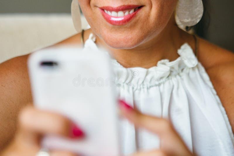 Unrecognizable uśmiechnięta kobieta używa smartphone zdjęcia royalty free