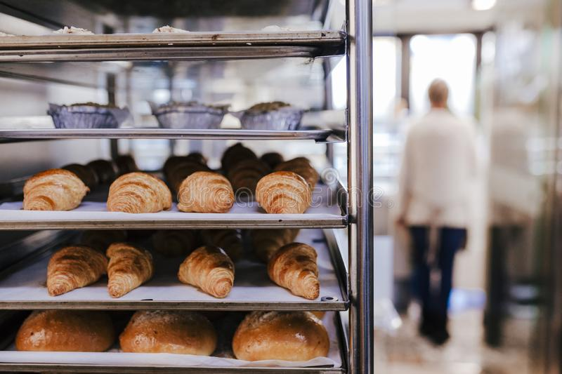 Unrecognizable woman on bakery. selective focus with croissants and bread stock photography