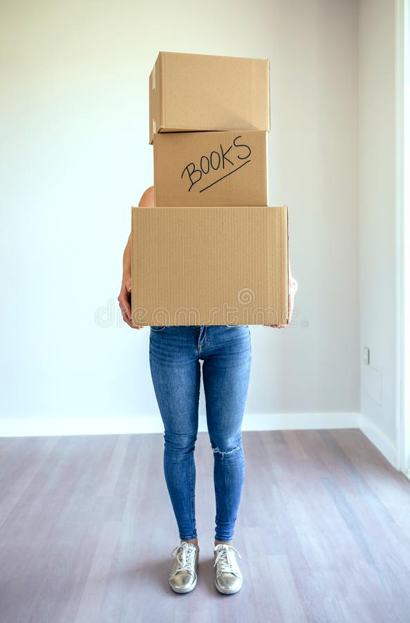 Unrecognizable woman carrying moving boxes stock photography