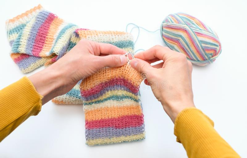 Unrecognizable woman engaged in needlework, knits a colorful scarf. royalty free stock images