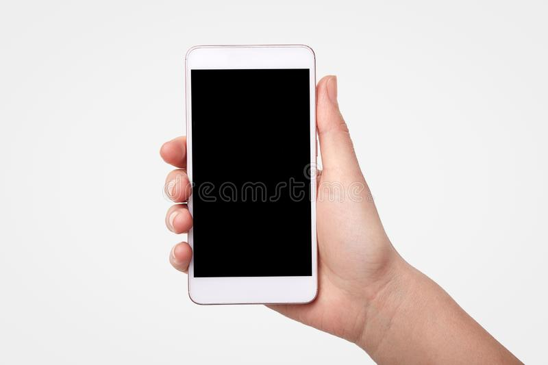 Unrecognizable woman holds smart phone with blank screen for your promotional content or advertisement, isolated over white royalty free stock photography