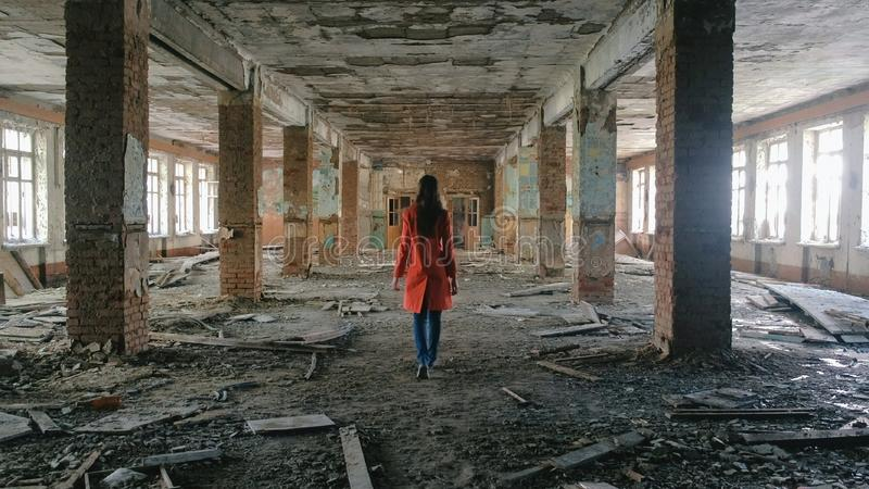 Unrecognizable woman in a red cloak inspects destroyed building after the disaster earthquake, flood, fire. royalty free stock image