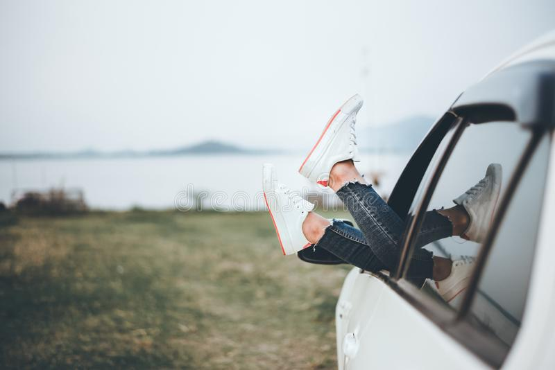 Unrecognizable woman resting with her feet up sitting on the passenger seat of the car. Freedom travel concept. Spending weekend. Unrecognizable woman resting royalty free stock photography