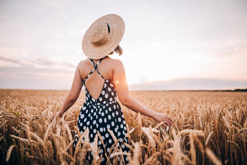 Unrecognizable woman in retro style dress and hat posing in wheat golden field. royalty free stock images