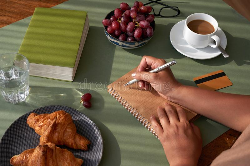 Taking Notes at Breakfast. Unrecognizable woman sitting at kitchen table and taking necessary notes, appetizing croissants and cup of fragrant coffee waiting for stock photos