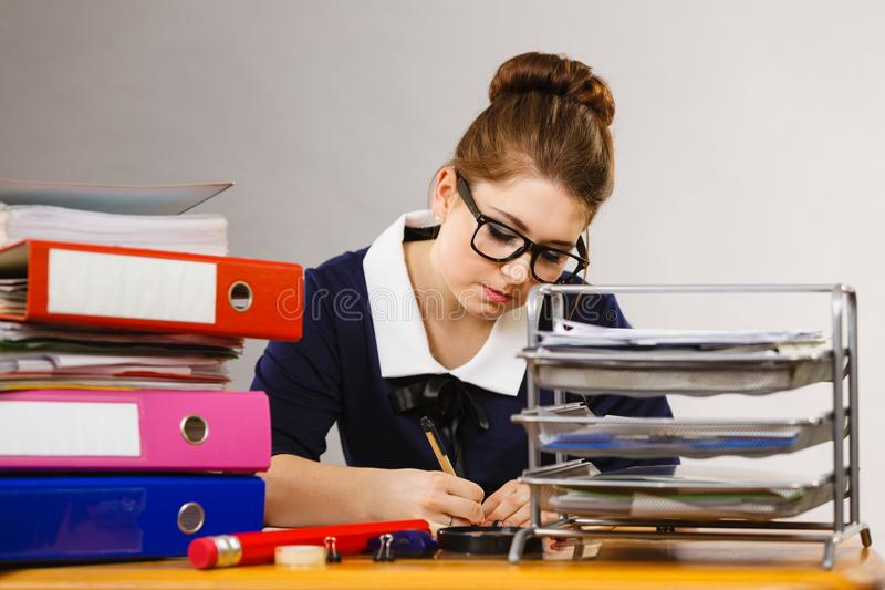 Business woman in office writing something down. Unrecognizable woman sitting working at desk full off documents in binders writing something down stock image