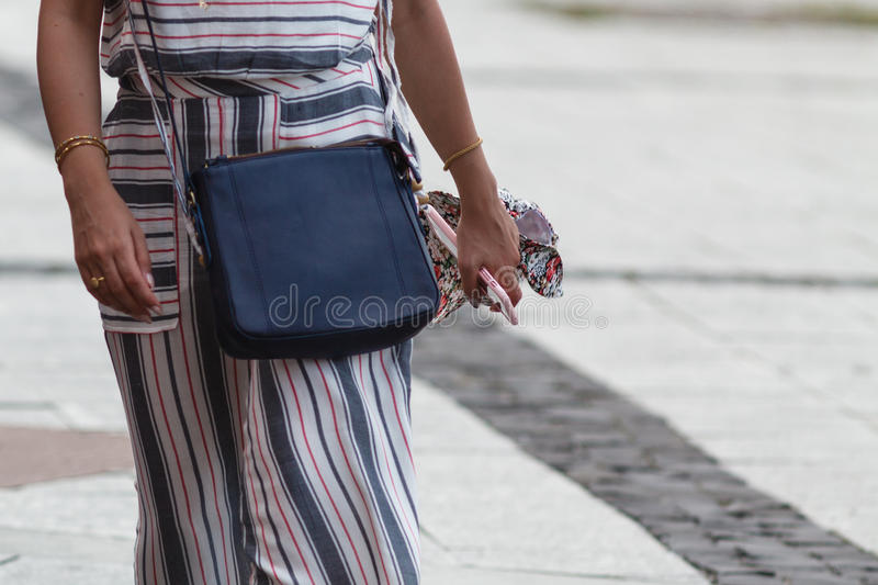 Unrecognizable woman in the street with her mobile phone in hand stock photography