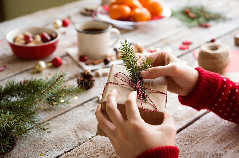 Unrecognizable woman wrapping and decorating Christmas present stock image