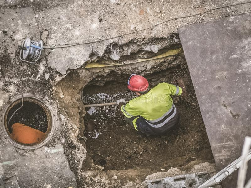 Unrecognizable workers repairing the sewage system royalty free stock photography