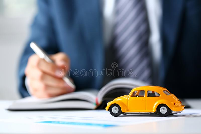 Unrecognizable yellow toy car on selling documents. Closeup with employee holding silver pen in background. Driver money loss prevention, carrier office, road stock image