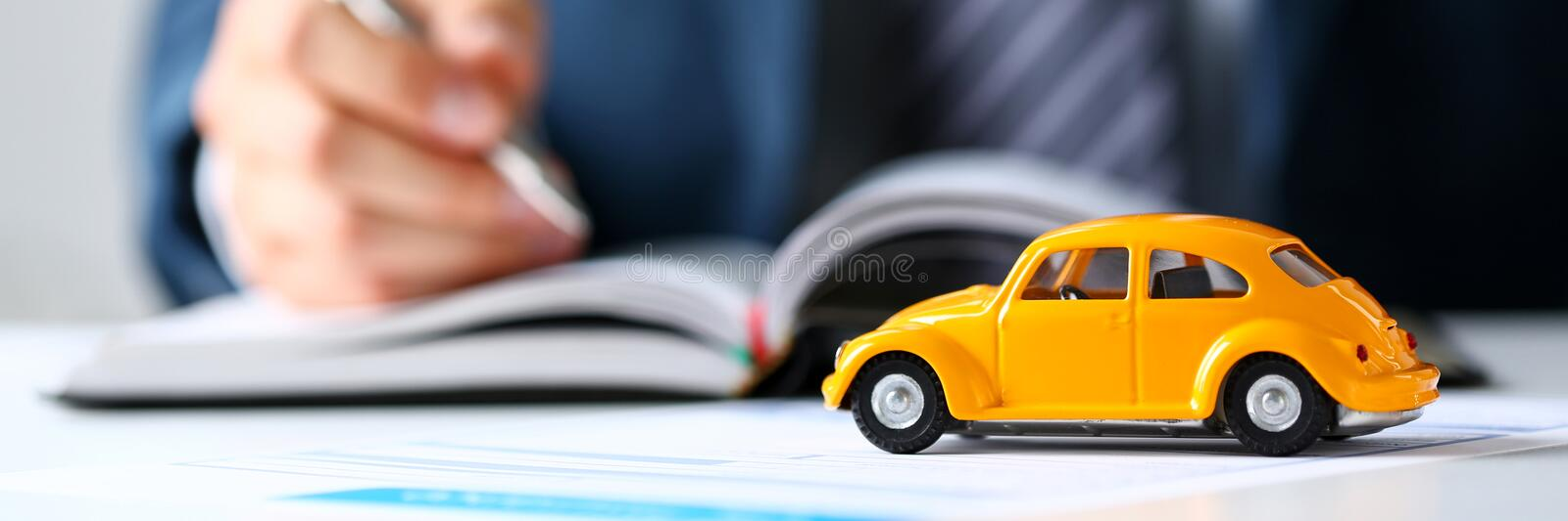 Unrecognizable yellow toy car on selling documents. Closeup with employee holding silver pen in background. Driver money loss prevention, carrier office, road stock photos