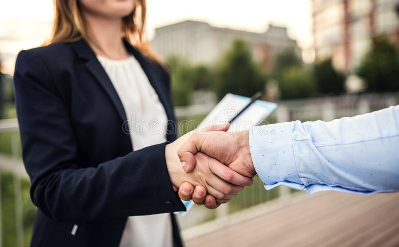 Unrecognizable young businessman and businesswoman shaking hands. An unrecognizable young businessman and businesswoman shaking hands royalty free stock image