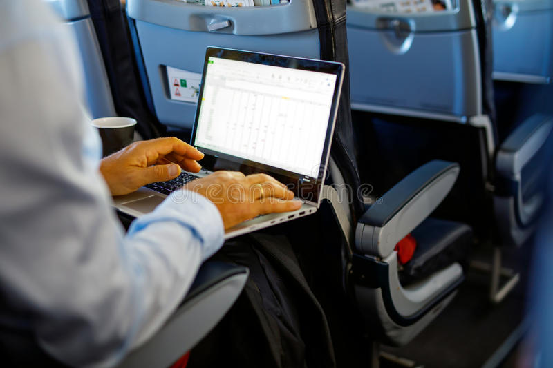 Unrecognizable young businessman with notebook sitting inside an airplane stock image
