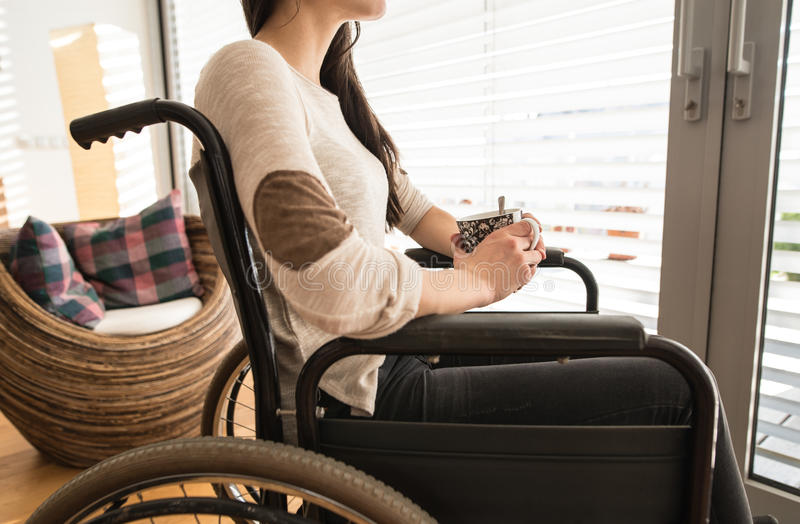 Unrecognizable young disabled woman in wheelchair at home. stock images
