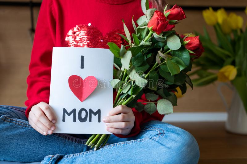 Unrecognizable young girl holding homemade greeting card and red roses for her mom. Happy Mother`s Day or Birthday Background. royalty free stock images
