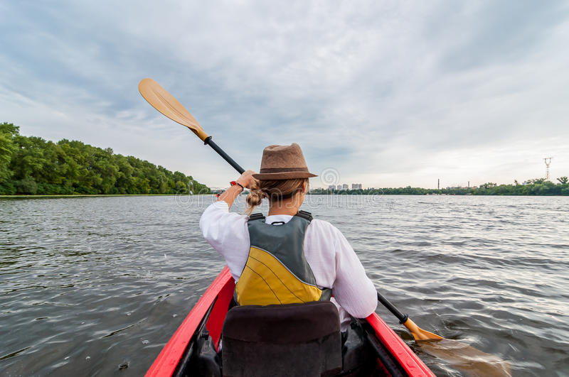 Unrecognizable Young girl kayaking on a river or lake. Happy girl canoeing on a summer day. royalty free stock image