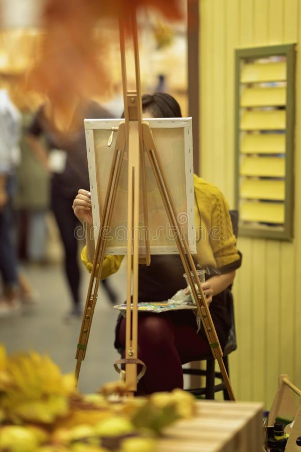 Unrecognizable young girl painting a picture of autumn on an easel, hands with brush and a palette of paints, concept of stock photo