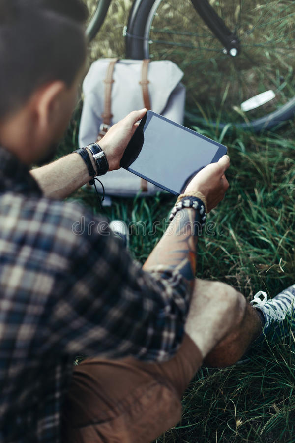 Unrecognizable Young Man Cyclist Sits On Summer Meadow Near Bicycle, Holding And Looking At Tablet Recreation Resting Travel. Unrecognizable young fellow stock image