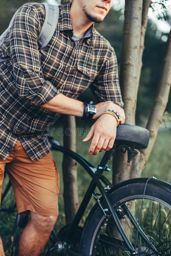 Unrecognizable Young Man Cyclist Standing With Bicycle Near Tree In Summer Park And Resting Recreation Travel Destination Concept. Unrecognizable young man royalty free stock photo