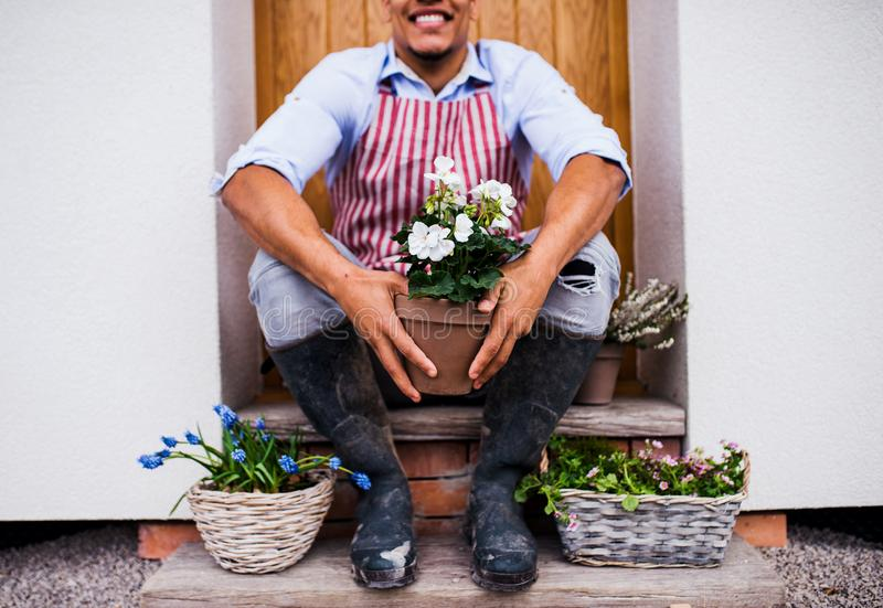 Unrecognizable young man gardener sitting in front of door at home. royalty free stock image