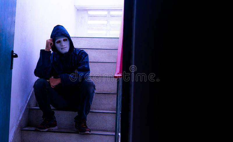 Unrecognizable young man white mask and hoodie sitting on old stairs,. Sadness, despair, dark, concept stock images