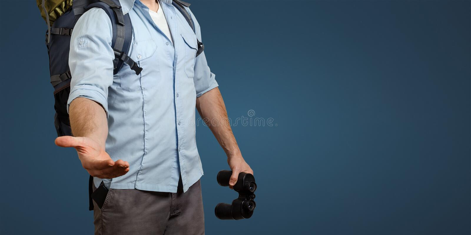 Unrecognizable Young Traveler Man With A Backpack And Binoculars On Blue Background. Stretches Out His Hand. Help In Travel Concep stock image