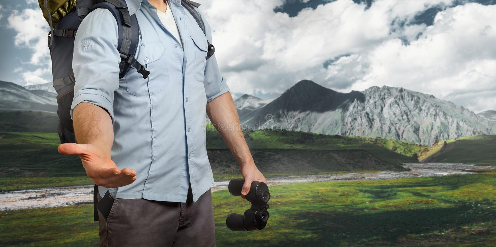 Unrecognizable Young Traveler Man With A Backpack And Binoculars, Stretches Out His Hand Mountains. Help In Travel Concept stock photography