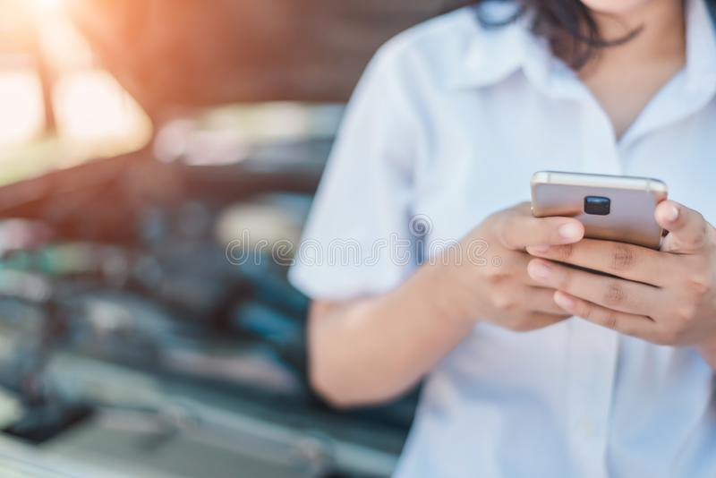 Unrecognizable young woman with broken down car calling by mobile phone royalty free stock images