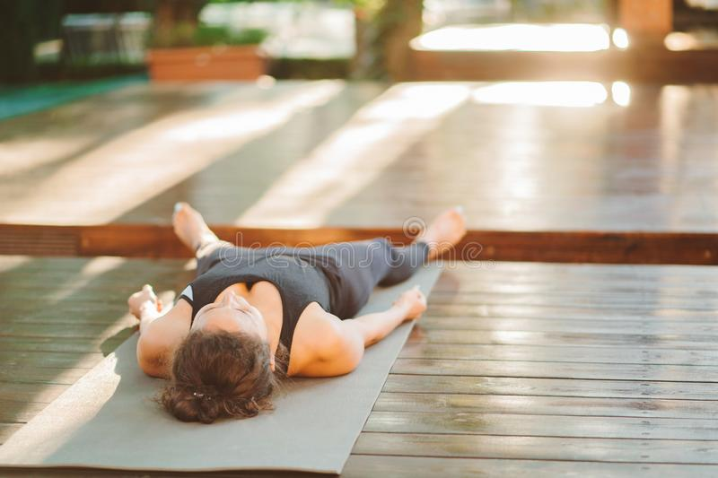 Unrecognizable young woman working outdoors, doing yoga exercise on grey mat, lying in Shavasana - Dead Body Posture royalty free stock images