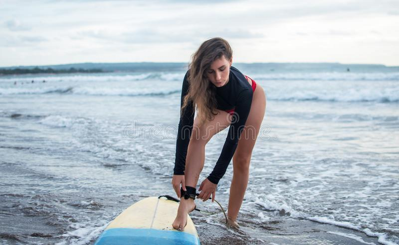 Unrecognizble har den barfota kvinnan fixat legrope, ställningar på sand nära surfingbrädan, skyddar sig från att krascha in i ku arkivbild
