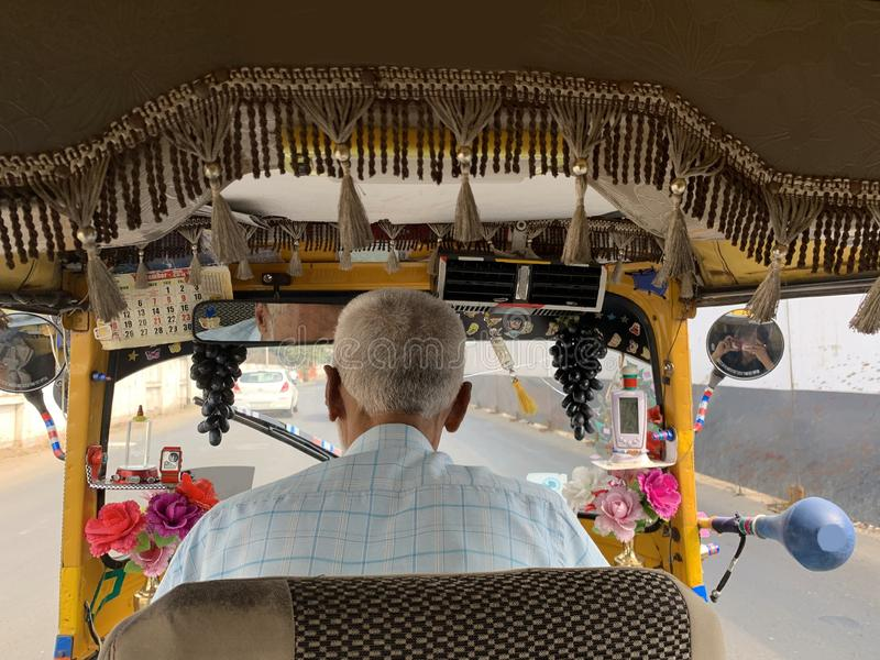 An unrecognized old man is driving well maintained and decorated auto rickshaw. Three wheeler auto rickshaw is a Very popular mode of transportation in India stock photo