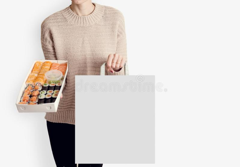 Unreconized kvinna som rymmer srt av kines för baner för website för utrymme för kopia för bakgrund för sushileveransmat vit royaltyfri fotografi