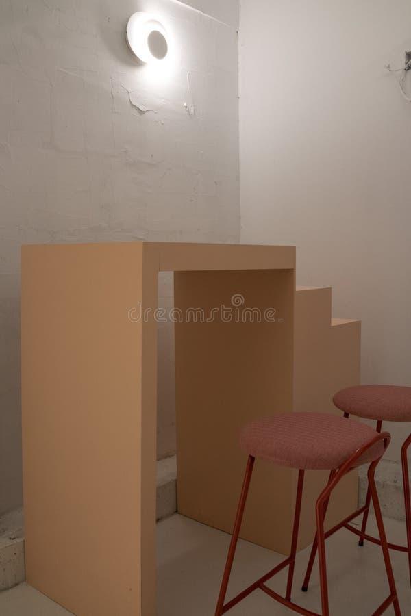 Unregelmäßige Tabelle und der rosa Schreibtisch Die Lampe auf der alten weißen Wand lizenzfreies stockfoto