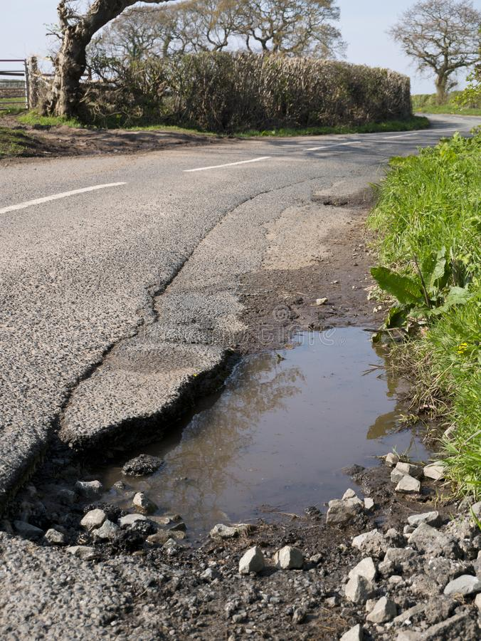 Unrepaired surface damage to tarmac on a rural road. Close view in portrait format of unrepaired surface damage to tarmac on a rural road in England, UK in early stock image