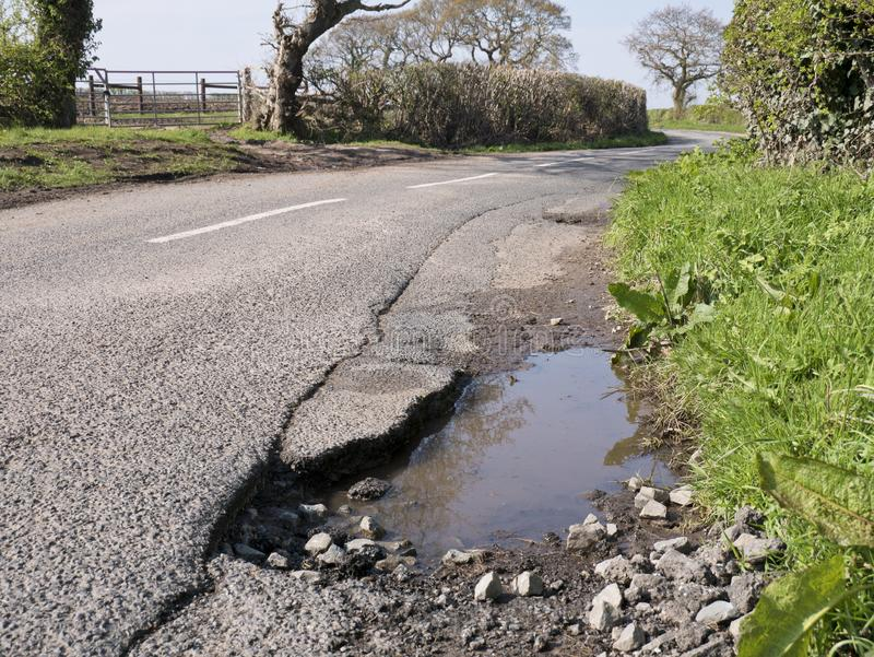 Unrepaired surface damage to tarmac on a rural road. In England, UK in spring, with no people or vehicles visible royalty free stock photos