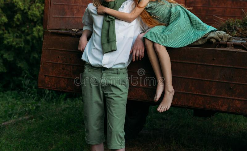 Unrequited first love. a barefooted girl in a green dress sits on the back of a car and hugs a barefoot, next to a standing guy, a. Unrequited first love. a royalty free stock photography