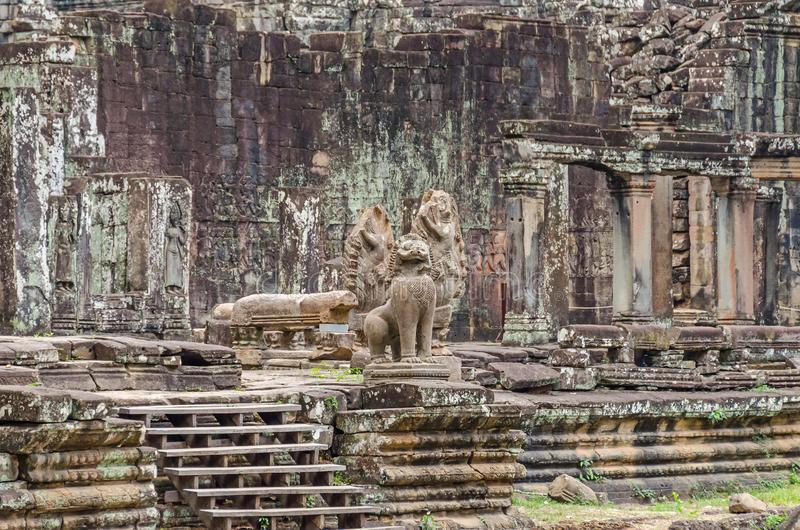 Unrestaured statues of a Cambodian naga, garudas and a lion in the Bayon temple in Angkor Thom royalty free stock photo