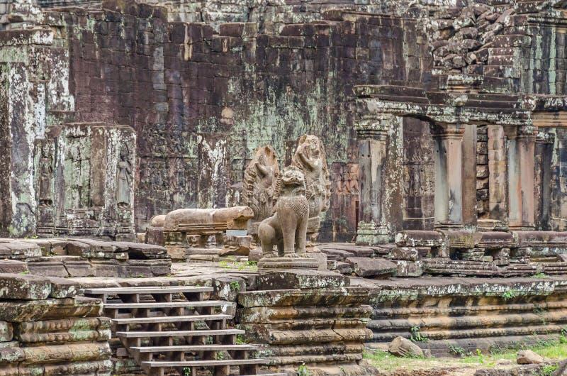 Unrestaured statyer av en kambodjansk naga, garudas och ett lejon i den Bayon templet i Angkor Thom royaltyfri foto