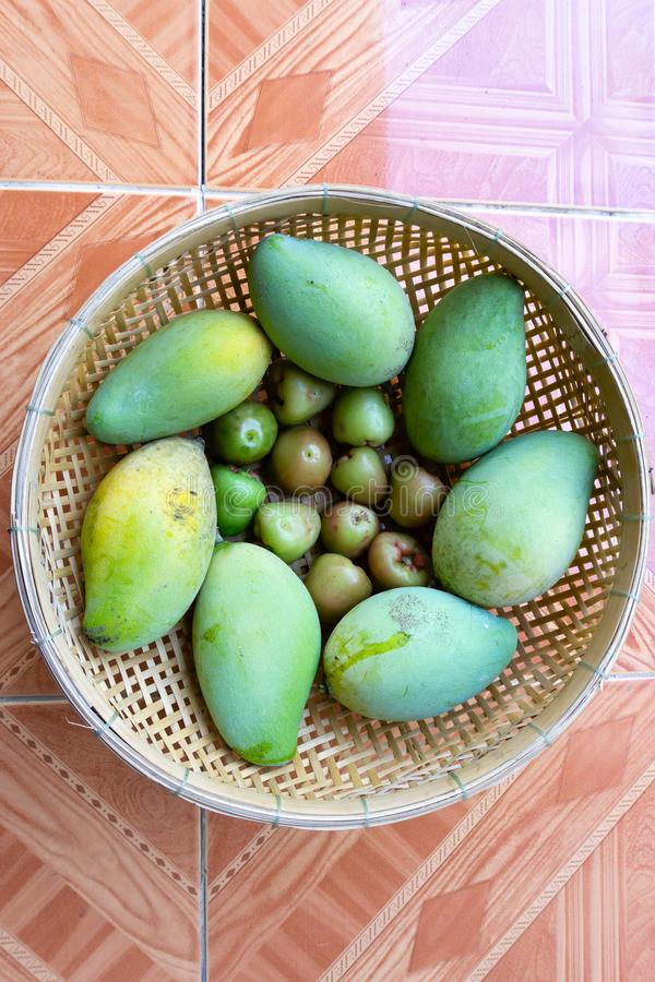 Unripe mango and plum in the basket royalty free stock photography