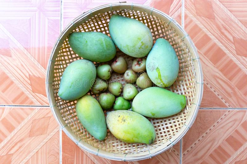 Unripe mango and plum in the basket royalty free stock photo