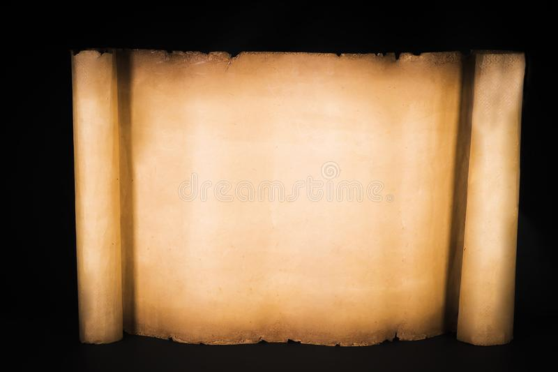 Unrolled papyrus scroll on a black background stock images