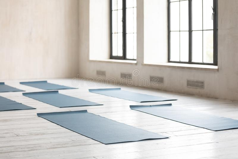 Unrolled yoga mats on wooden floor in empty fitness center royalty free stock photo