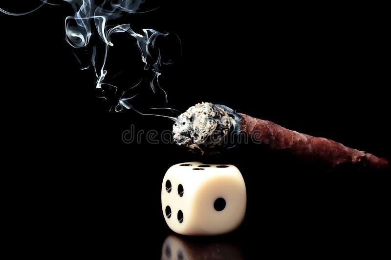 Uns dado e charuto brancos com fumo no fundo preto foto de stock royalty free