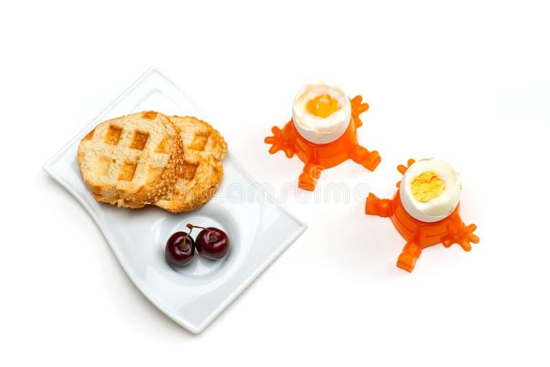 Uns dois de ovos cozidos e quentes estão em uns copos de ovo, ao lado dele são uma placa com uns dois dos brindes e umas duas das foto de stock royalty free