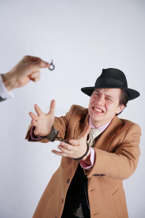Uns homem prenderam outro pondo sobre as algemas de aço de uma polícia e trocista mostrando lhe a chave e amam a liberdade fotos de stock royalty free
