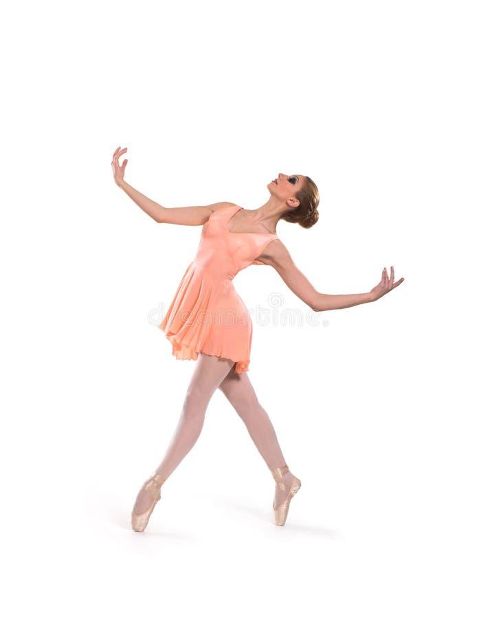 Uns jovens e um dançarino de bailado fêmea do ajuste em um vestido alaranjado imagem de stock royalty free