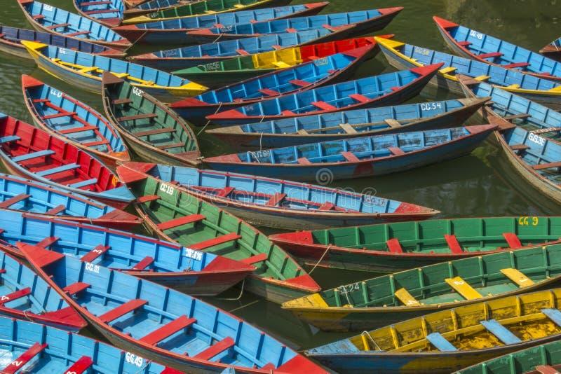 Uns lotes de barcos coloridos de madeira velhos na água barcos verdes e amarelos vermelhos azuis no lago imagem de stock royalty free
