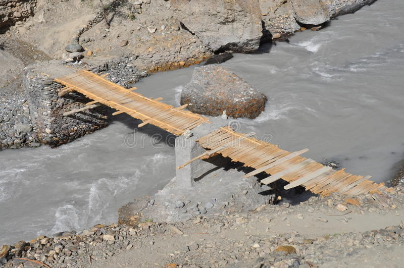 Unsafe bridge. Very unsafe and dangerous wooden bridge on the river royalty free stock images