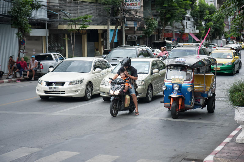 Unsafe father and son on motorbike. Bangkok, Thailand - July 19, 2015: Unsafe little boy not wearing a helmet sits in front of father on motorbike waits for stock images