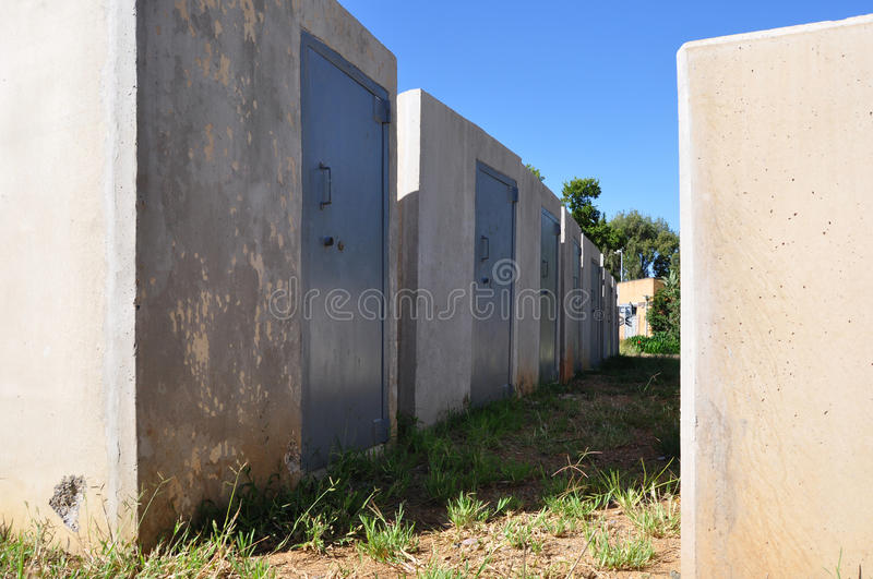 Unsafe Safe. A grouping of abandoned heavy duty safes with grass growing all round the base. Concrete and steel construction. An unsafe investment or ineffective stock photography